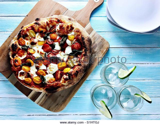 Pizza with cherry tomatoes, mozzarella, basil, and tomato sauce on picnic table. - Stock Image