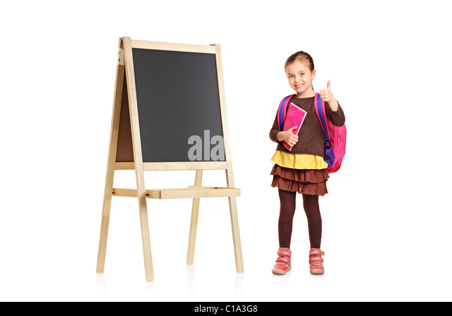 A child next to an empty school board holding book and showing thumb up - Stock Image