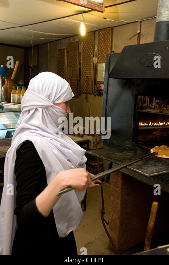 Young woman baking a manaeesh in bakery in Batloun, Shouf Mountains in Lebanon. - Stock Image