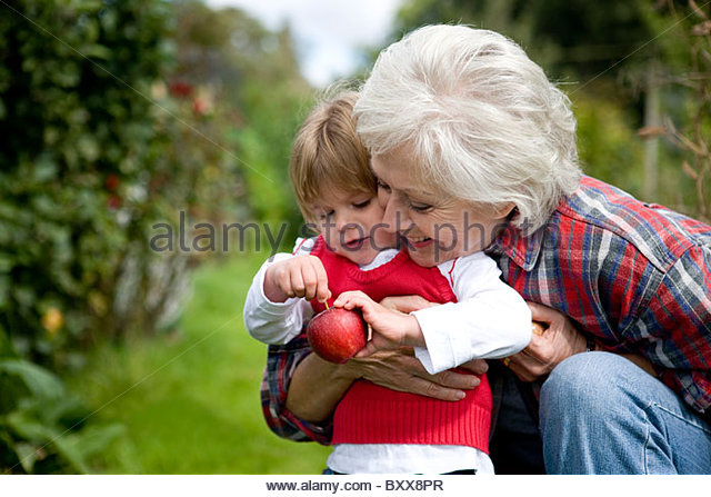A grandmother and granddaughter holding an apple - Stock Image