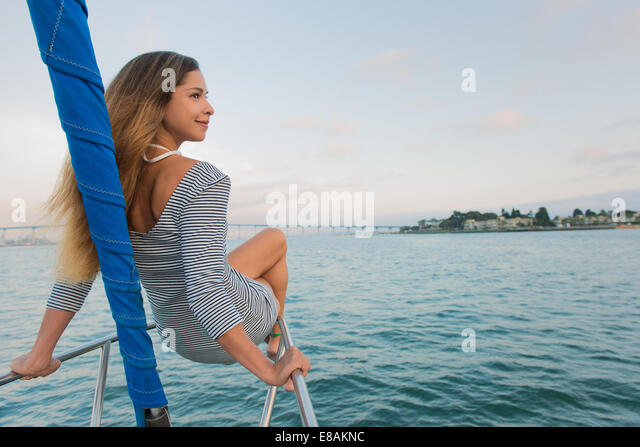 Mid adult woman sitting on railing on sailing boat - Stock Image