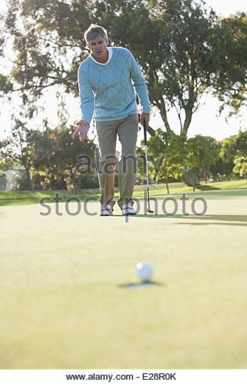 Man sinking golf ball into hole - Stock Image