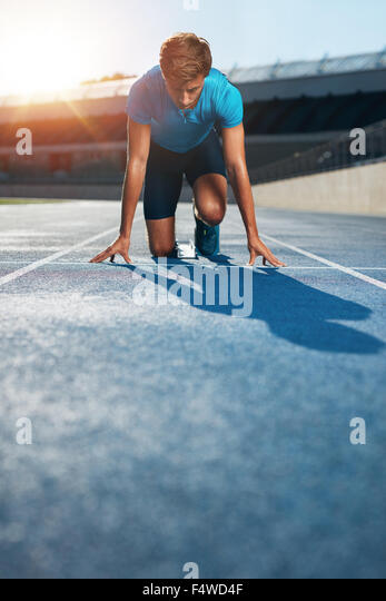 Professional male track athlete in set position on sprinting blocks of an athletics running track in stadium. - Stock Image