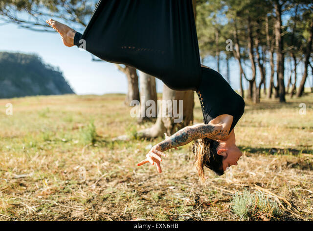 Woman practicing aerial yoga outdoors - Stock Image