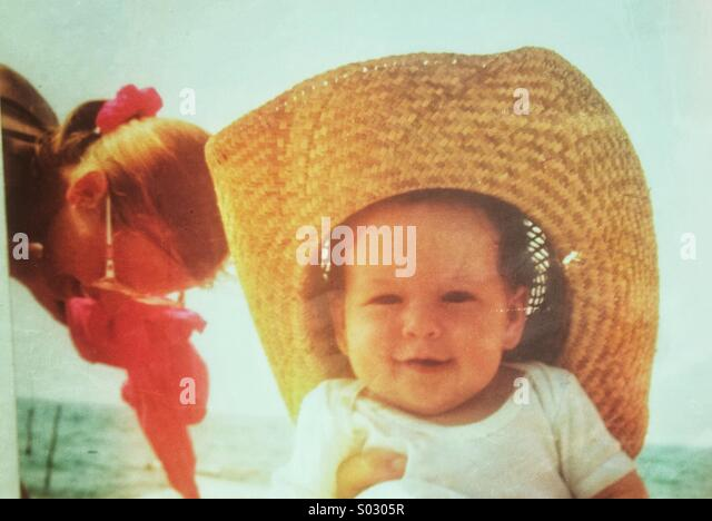 Baby aged 3-6 months with straw hat at the beach - Stock Image