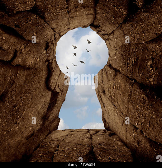 Key opening concept and the secret of success symbol as a mountain ciff shaped as a keyhole with birds flying away - Stock Image