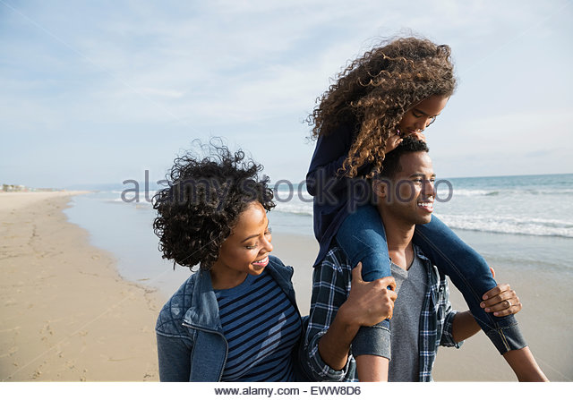 Family walking on sunny beach - Stock Image