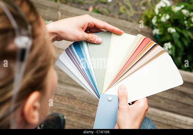 Woman looking at color swatch - Stock Image