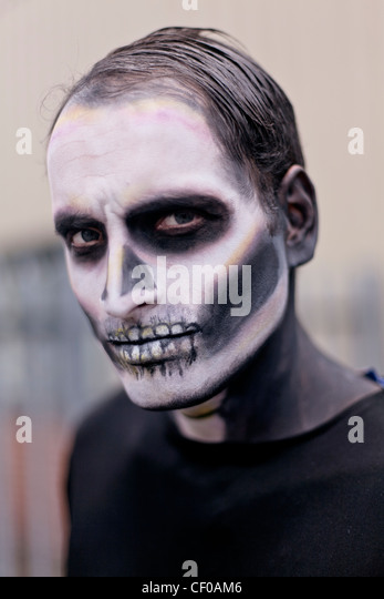 man made up with face paint to look like a scary skeleton - Stock Image