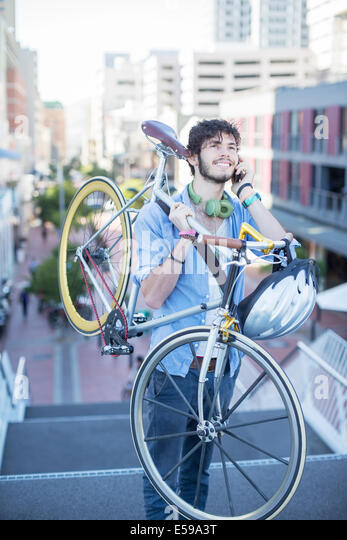 Man carrying bicycle on city steps - Stock Image