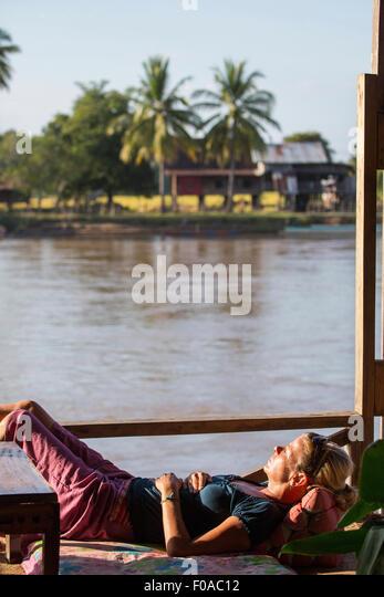 Female tourist sunbathing on Mekong houseboat, Don Det, Laos - Stock-Bilder