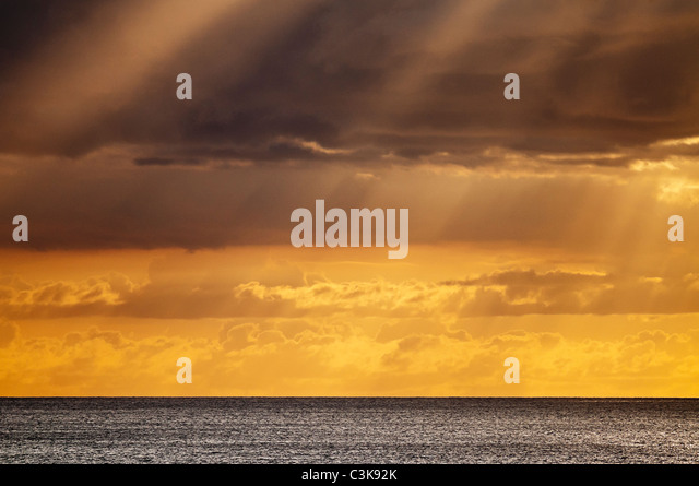 A colorful golden sunset with clouds off of Waikiki beach, Honolulu, Hawaii. - Stock Image