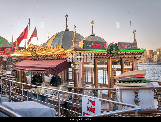 Istanbul, Turkey - April 25, 2017: Chefs preparing food in a traditional fast food bobbing boat serving fish sandwiches - Stock Image
