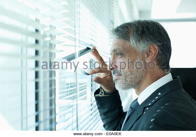 Portrait of confident businessman at window - Stock Image