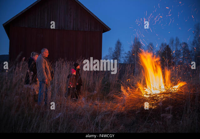 Sweden, Narke, Filipshyttan, Grandfather with grandchildren (6-7,8-9,16-17) looking at bonfire - Stock Image
