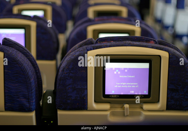 Row of seats and entertainment system of a commercial airplane - Stock Image