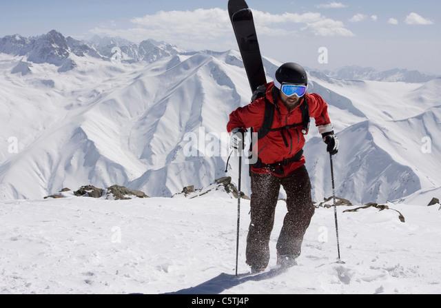 India, Kashmir, Gulmarg, Man with skis on back going uphill - Stock-Bilder