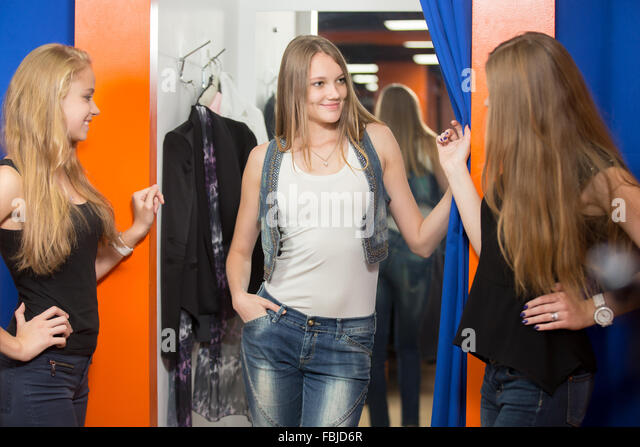 Group of three girlfriends shopping together. Cheerful young beautiful woman wearing jeans and denim vest standing - Stock Image