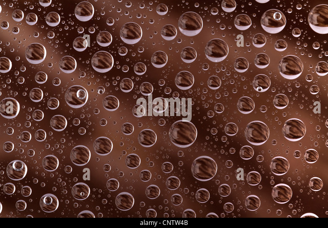 water drops over brown background, on the glass surface - Stock-Bilder