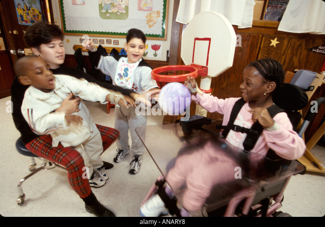 New Jersey East Orange Cerebral Palsy Center disabled student female therapist Black girl wheelchair boy wheelchair - Stock Image