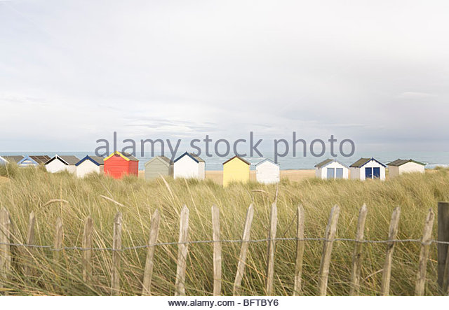Beach huts behind fencing - Stock Image