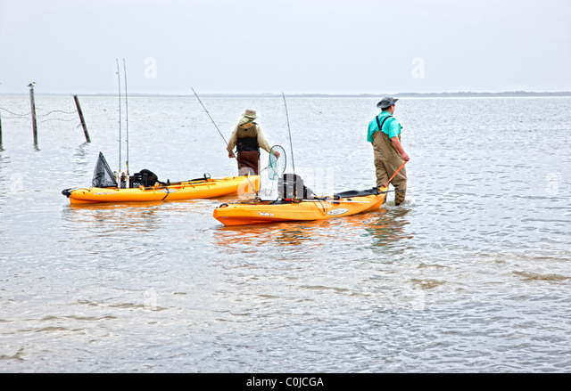 Fishermen launching kayaks, - Stock Image