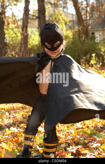 Kid dressed up like batman playing in the leaves - Stock Image