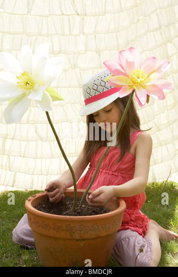 Girl playing with fake flowers in a flower pot - Stock Image
