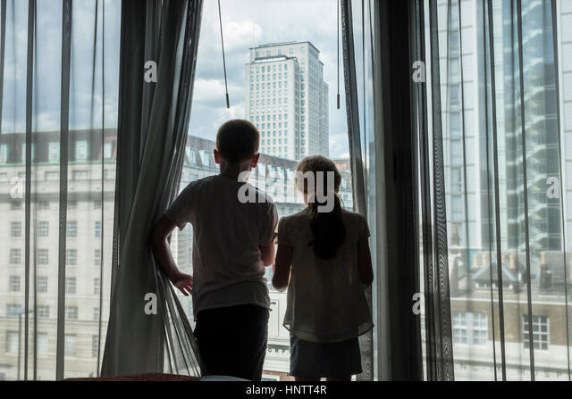 A boy and girl looking through a high window in a city. - Stock Image