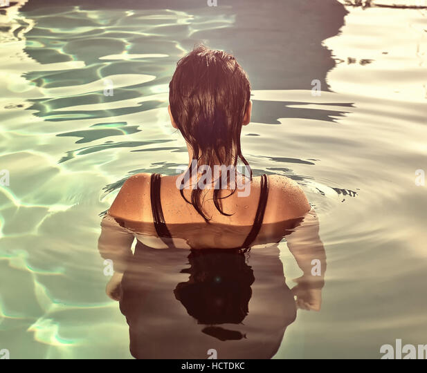 Girl swimming underwater in pool - Stock Image