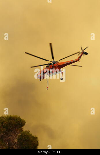 Aerial fire fighting a bush fire using water bomber helicopter in Western Australia. - Stock Image