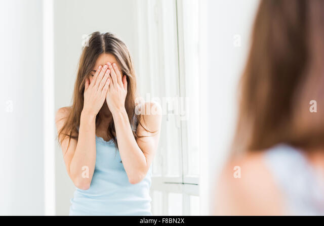 Woman hiding her face with her hands . - Stock Image