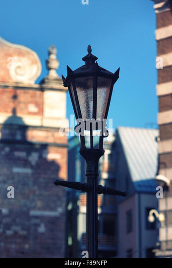 Stylish street light on the background of old houses and churches in the middle of Riga - Stock Image