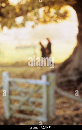 Defocussed couple walking past a giant oak tree and gated fence in autumn or fall - Stock-Bilder