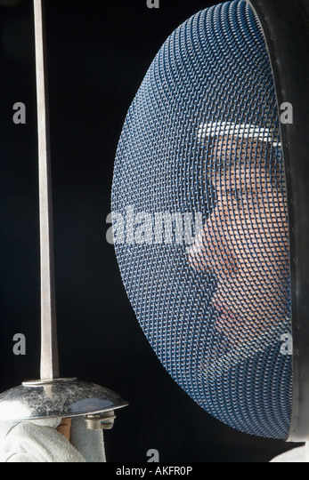 Side profile of a male fencer holding a fencing foil - Stock Image