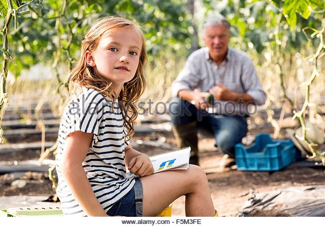 Girl sitting drawing while grandfather works looking at camera - Stock-Bilder