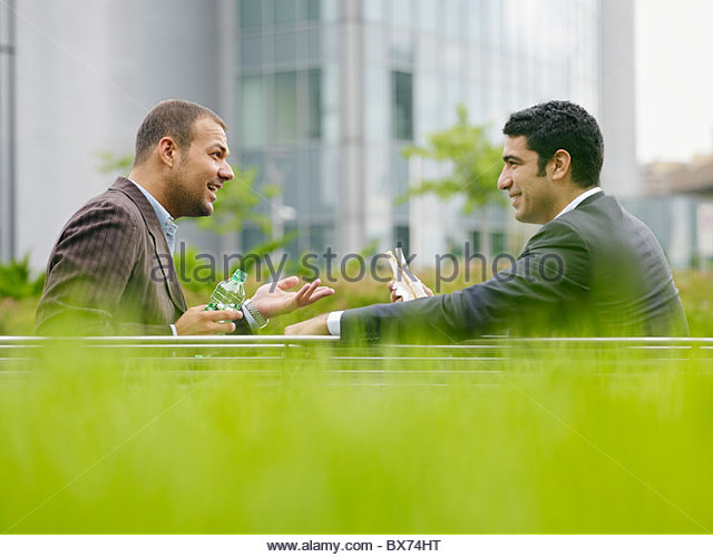Businesspeople eating outdoors - Stock Image