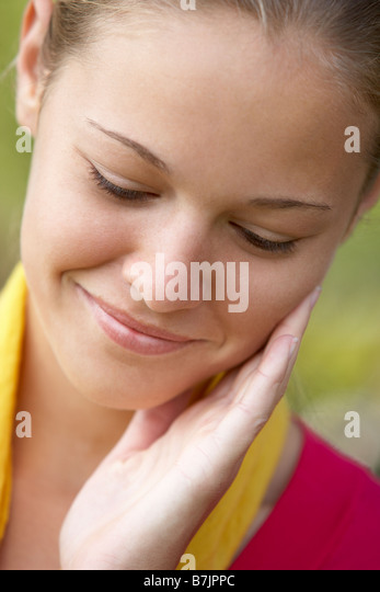 Portrait Of Teenage Girl Resting Head In Hands And Smiling - Stock Image