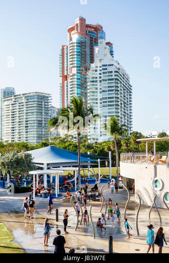 Miami Beach Florida South Pointe Park children's playground fountain splash pad playing children families buildings - Stock Image