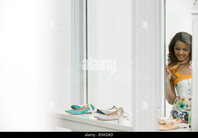 Young woman looking at shoes in shop window - Stock Image