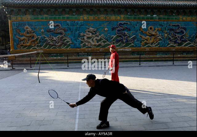 Two men play badminton in the morning in front of Nine Dragons Wall at Beihai Park in Beijing, China. 17-Feb-2008 - Stock Image