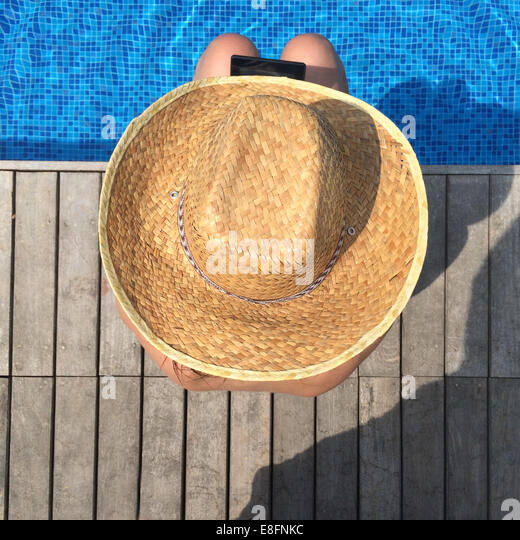 Overhead view of Woman with digital tablet sitting at the edge of swimming pool - Stock Image