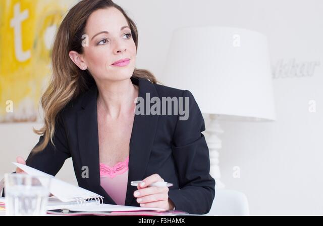 Mature woman wearing business attire holding pen and paperwork looking away smiling - Stock Image