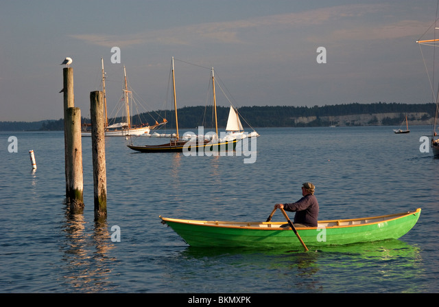 man in rowboat in bay with sailboat - Stock Image