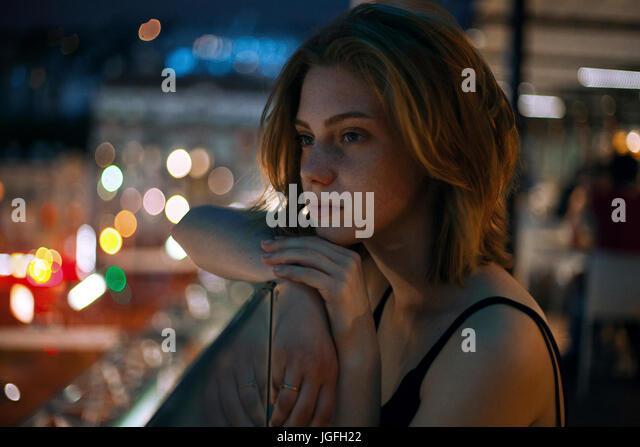 Pensive Caucasian teenage girl leaning on railing - Stock Image