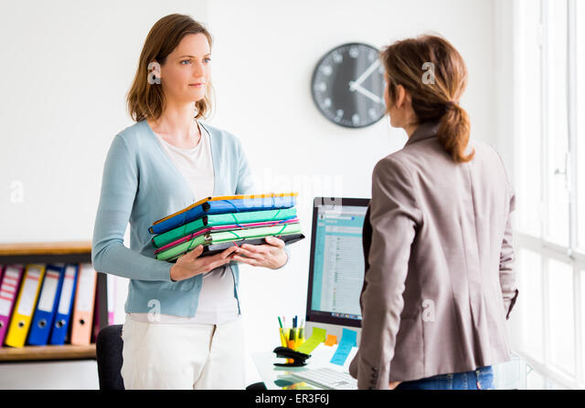 Women discussing at work. - Stock Image
