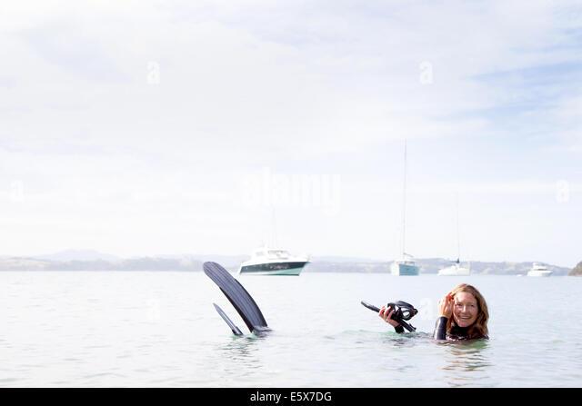 Portrait of mid adult female scuba diver in sea - Stock Image