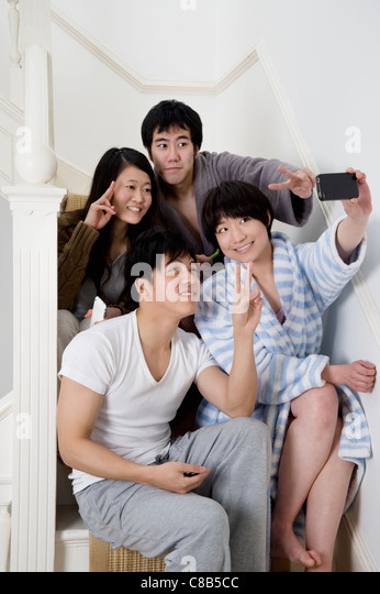 Young friends gesturing peace sign while taking self photograph - Stock-Bilder