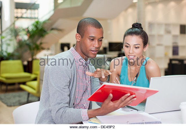 Businessman and businesswoman with laptop and digital tablet in office - Stock Image