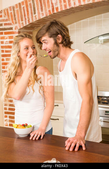 Cute couple eating a bowl of fruit salad - Stock Image